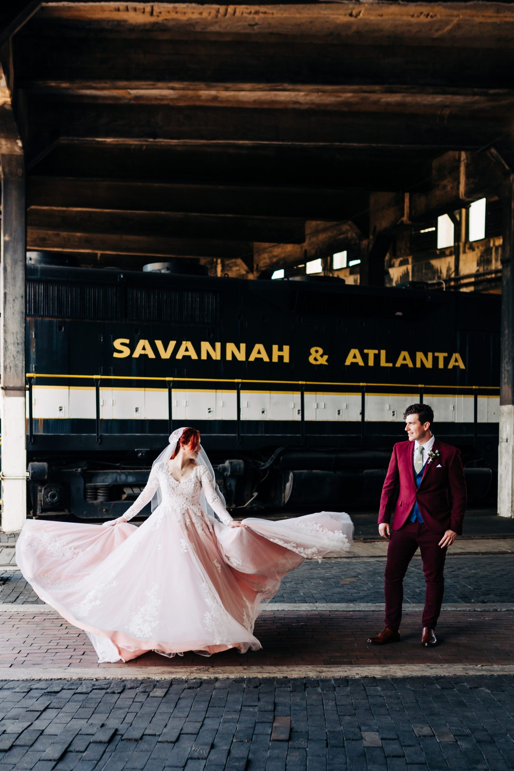 bride in long sleeved blush gown and cathedral veil spinning next to groom in custom fitted maroon suit at the Georgia state railroad museum in savannah