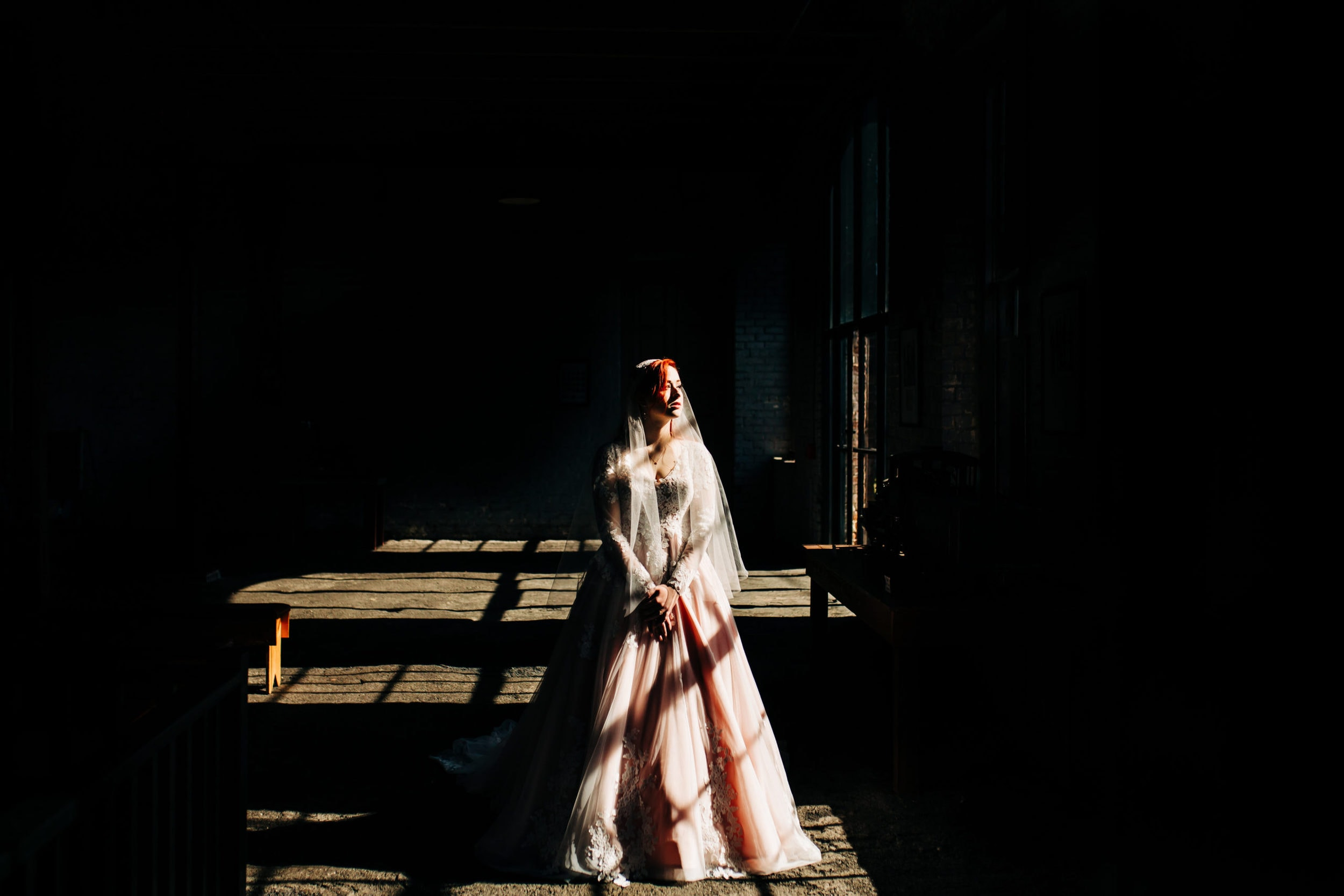 bride in long sleeved blush dress standing dramatically in window light surrounded by darkness at the Georgia state railroad museum