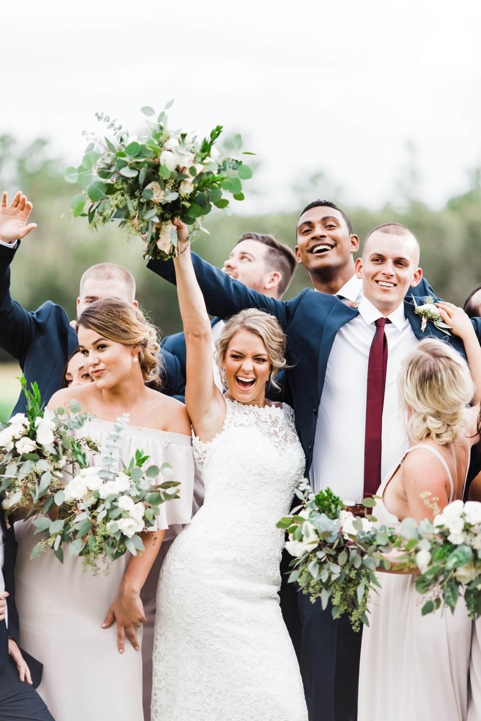 bride cheering while standing with her groom and formal party