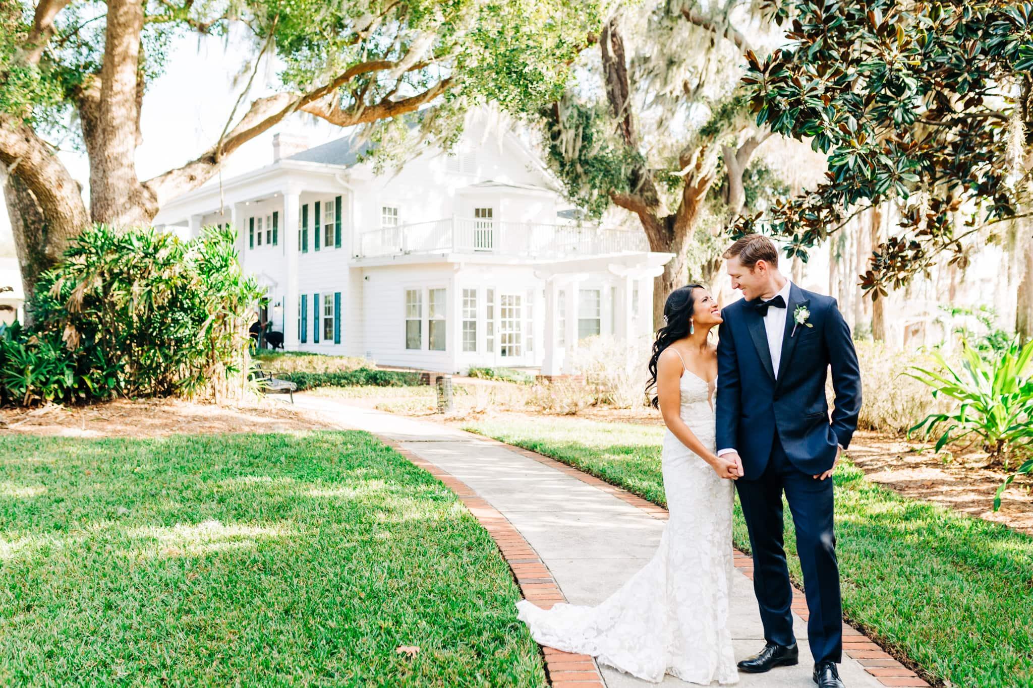 bride and groom standing close together in front of cypress grove estate house underneath the oak trees with wedding venue in background