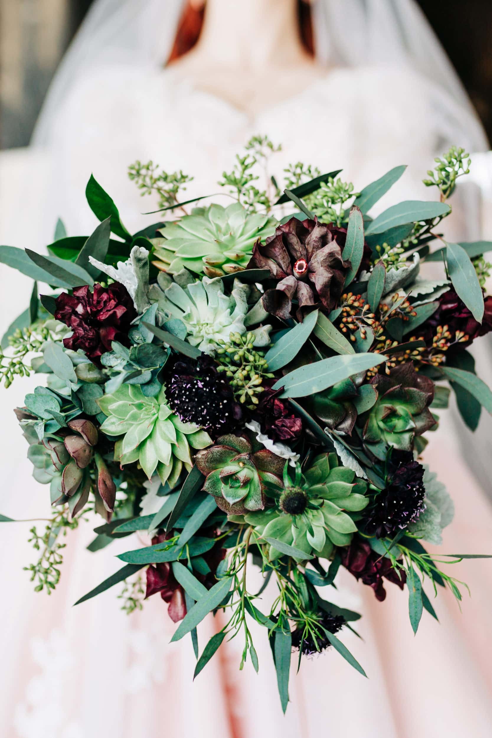 succulent bridal bouquet in green and purple hues with bride in soft focus in the background