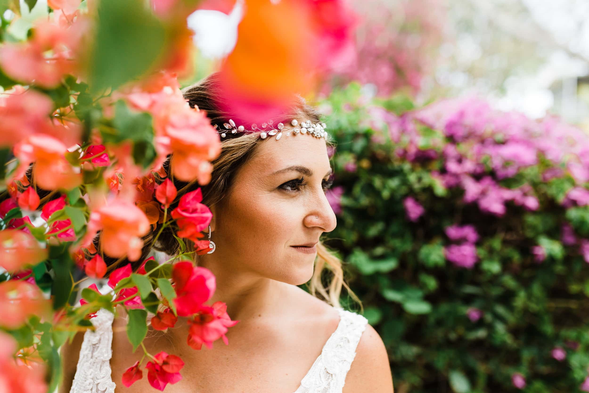 boho bride wearing bead crown standing among pink and fuchsia flowers with purple and green in the background