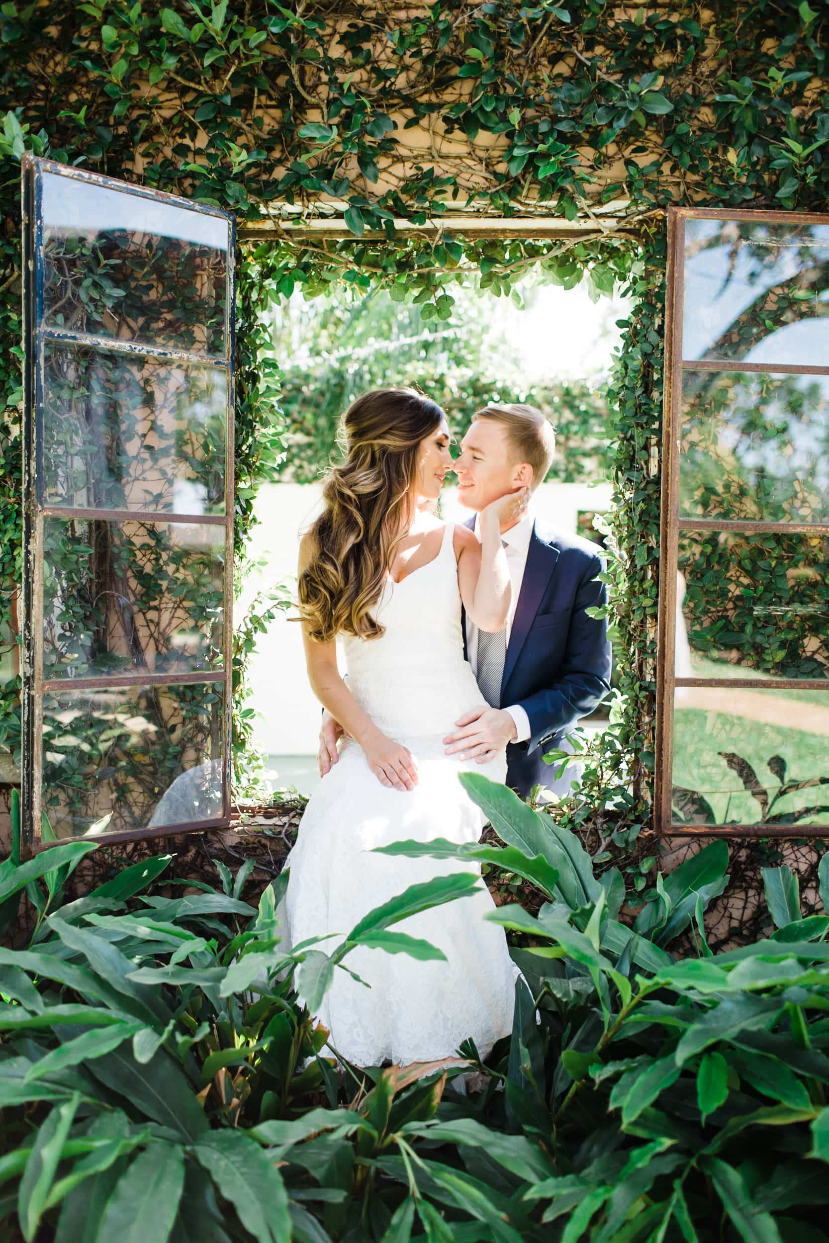 bride sitting on a windowsill embracing her groom on an ivy covered wall