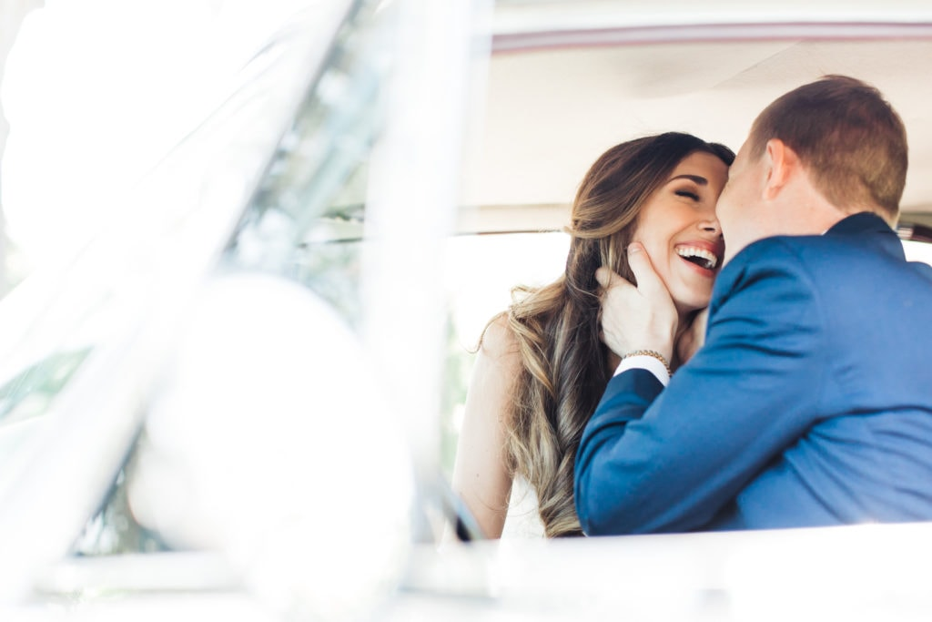 bride laughing while being kissed by groom in vintage car in front of the acre wedding venue in orlando florida