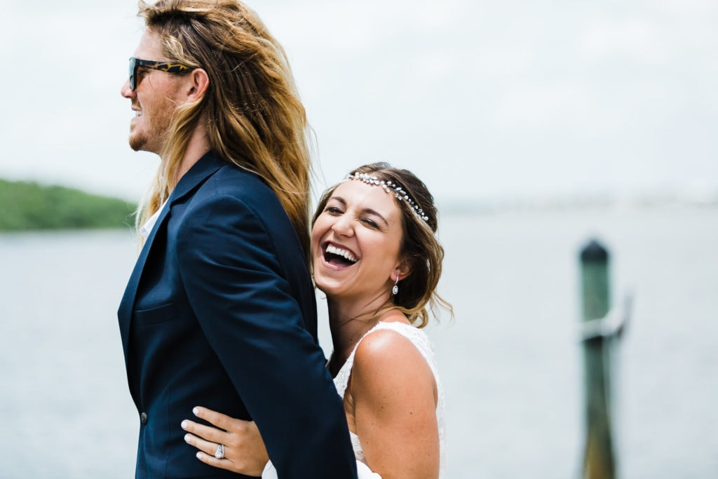 boho bride holding on to groom from behind during first look on the dock of the coconut palm inn and laughing