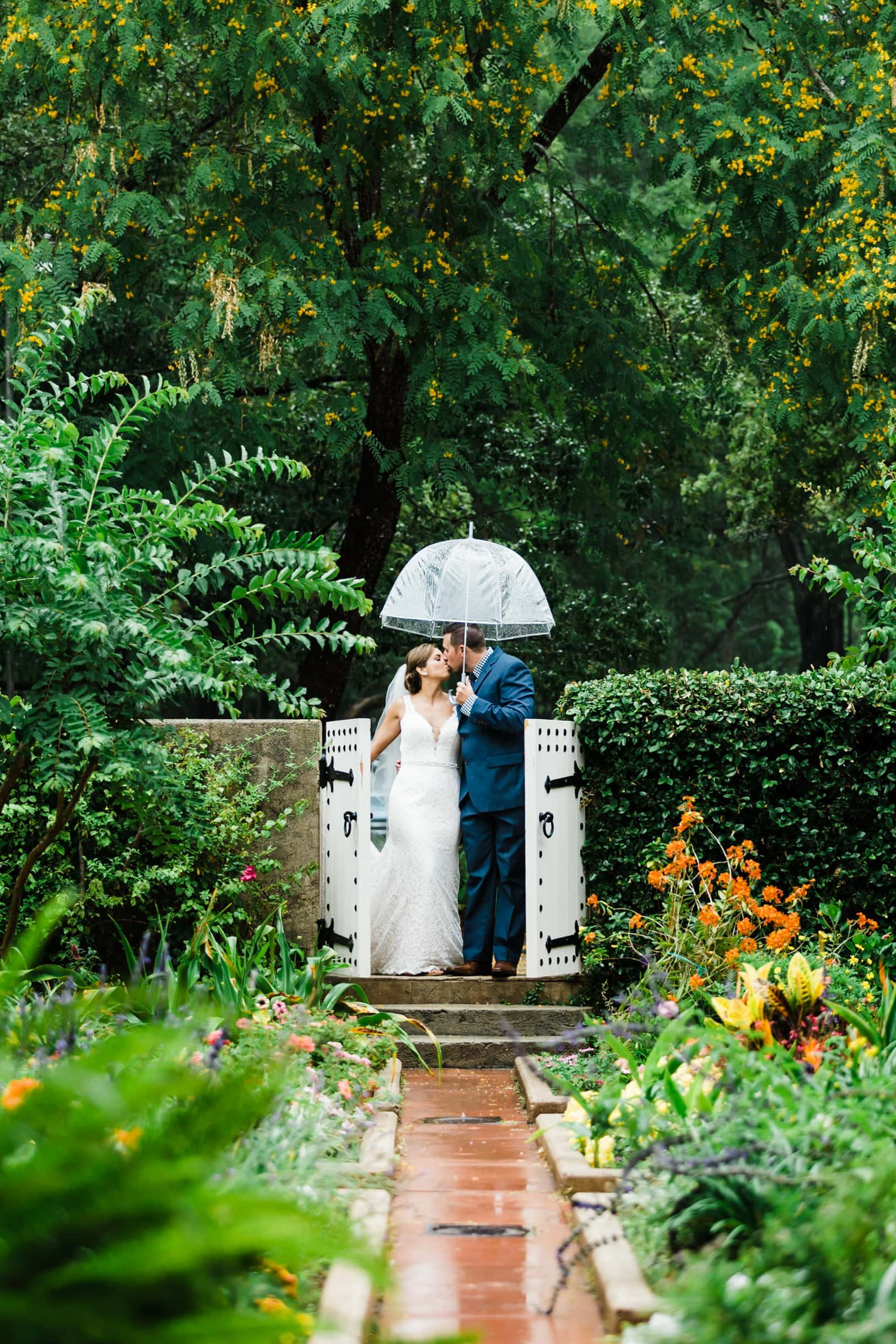 bride and groom kissing under clear bubble umbrella under the rain with lush green gardens surrounding them at sydonie mansion