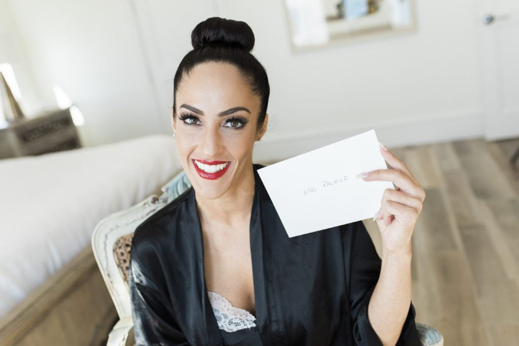 bride with red lips and big top bun holding onto note for groom and smiling