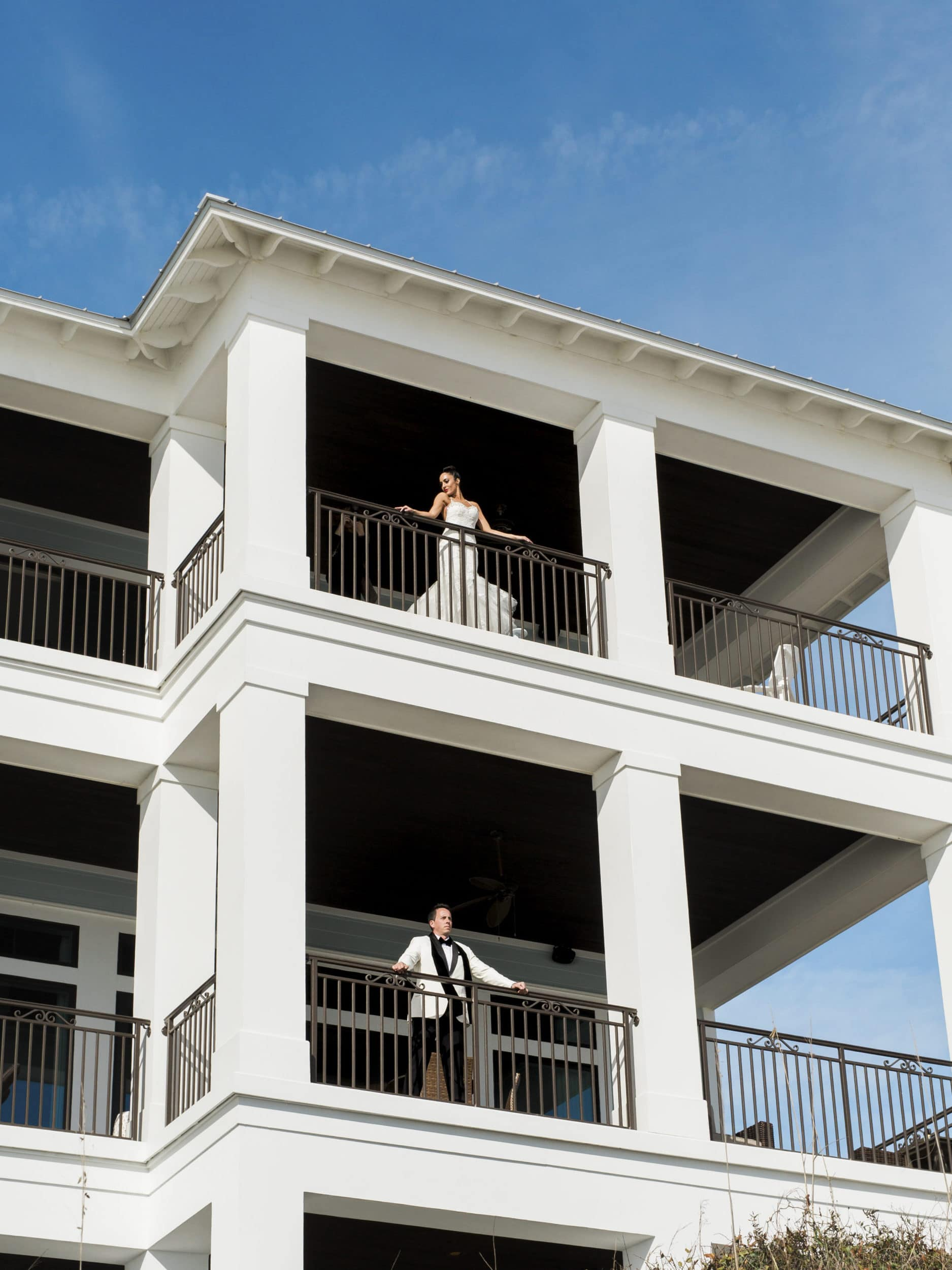 bride standing on a third floor balcony overlooking the ocean with the groom looking out of the second floor patio