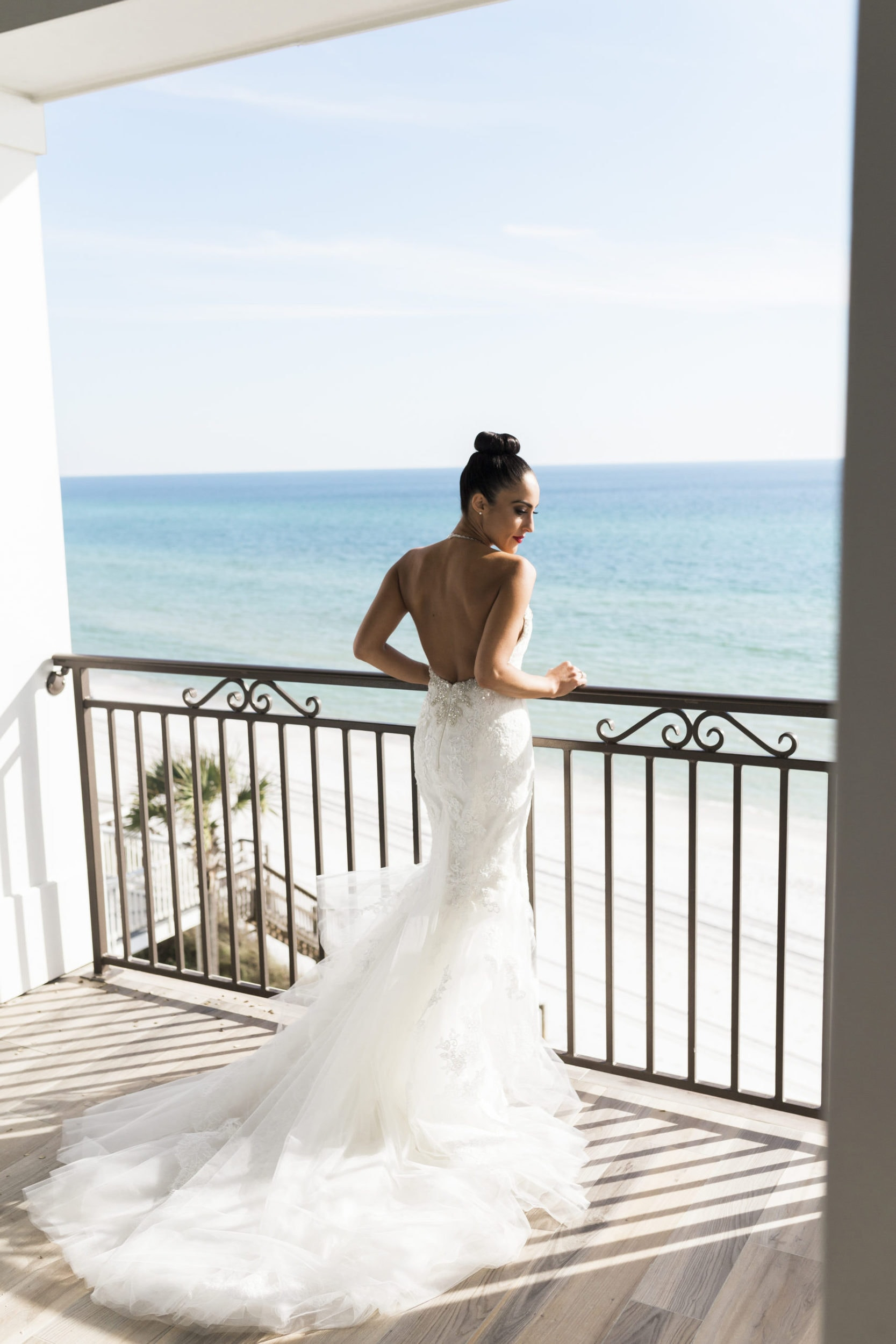bride in pronovias gown and top bun looking out at the ocean on a second floor balcony at rosemary beach