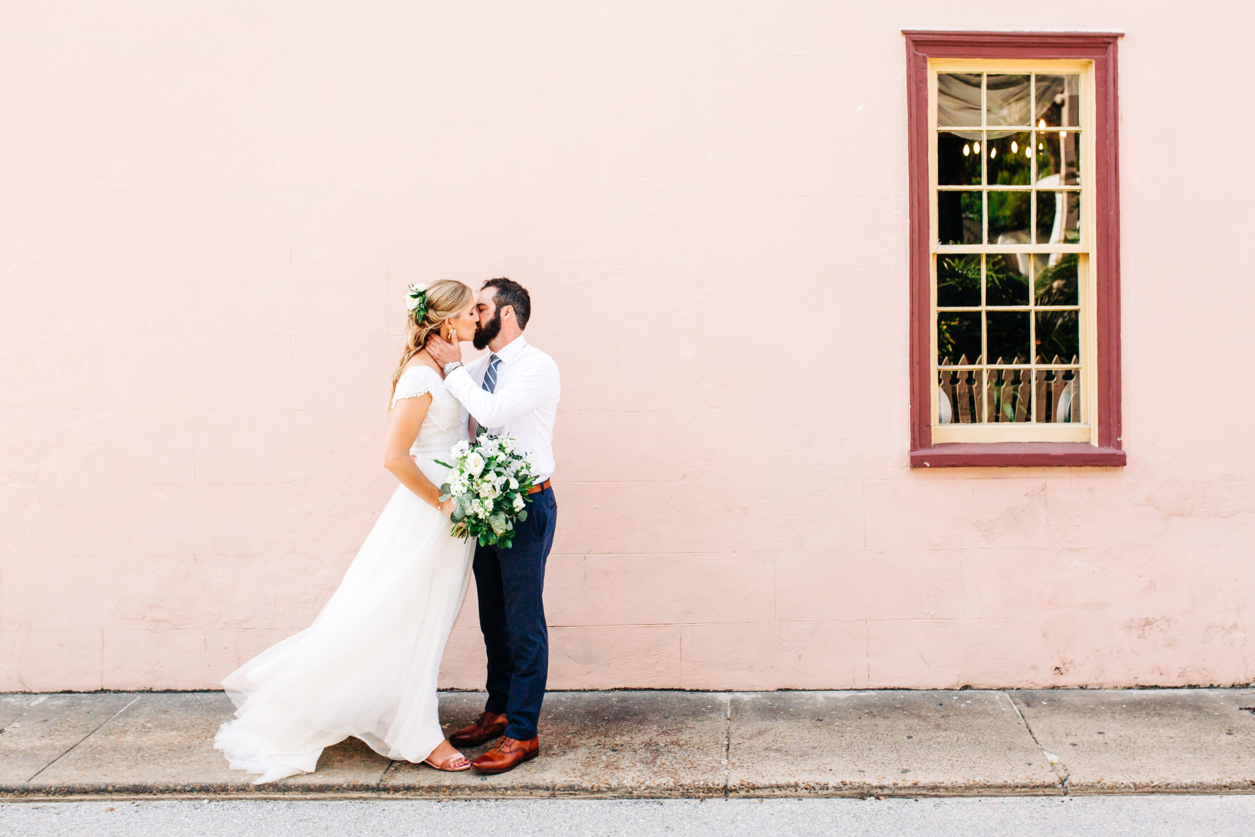 bride and groom kissing in front of pink wall in saint Augustine florida with dress fluttering in background and red side window