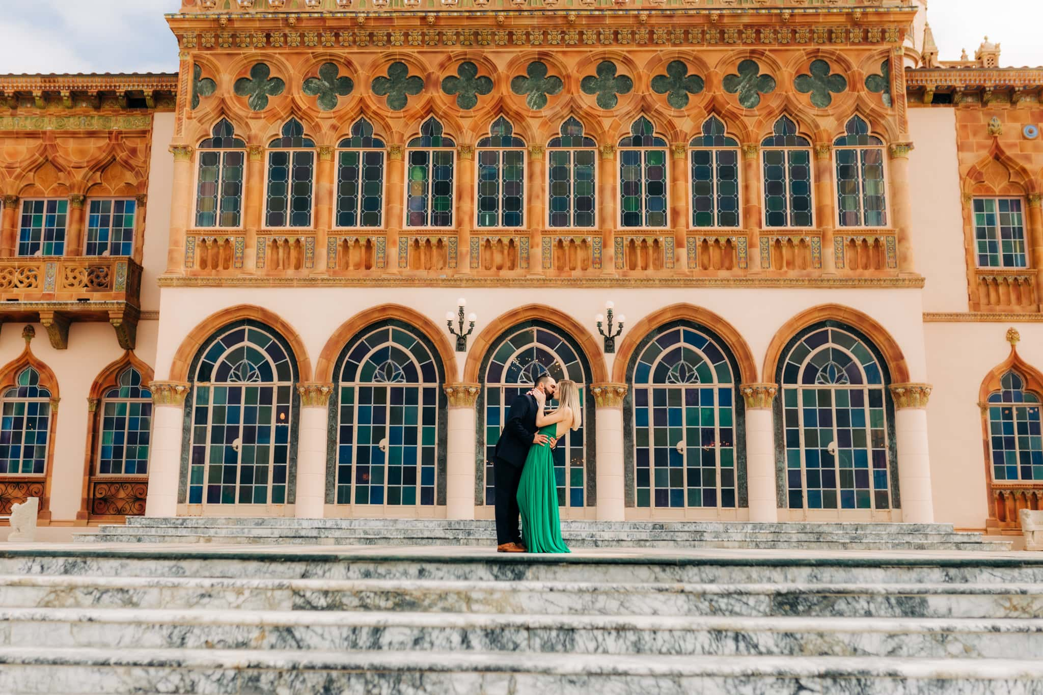 girl in green dress being kissed by groom in blue suit in front of the ringling museum