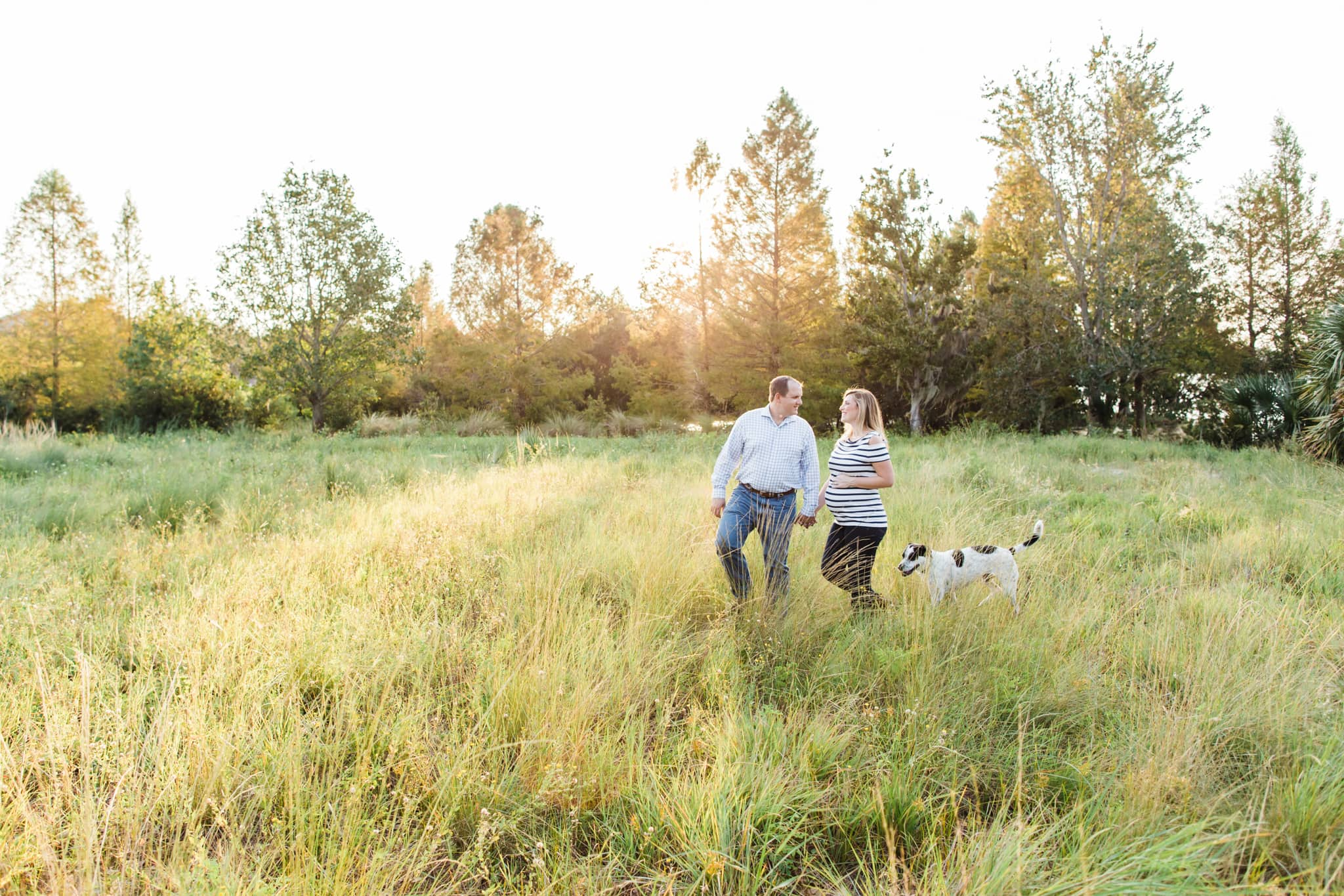 pregnant woman walking with husband and dog through field at Baldwin park