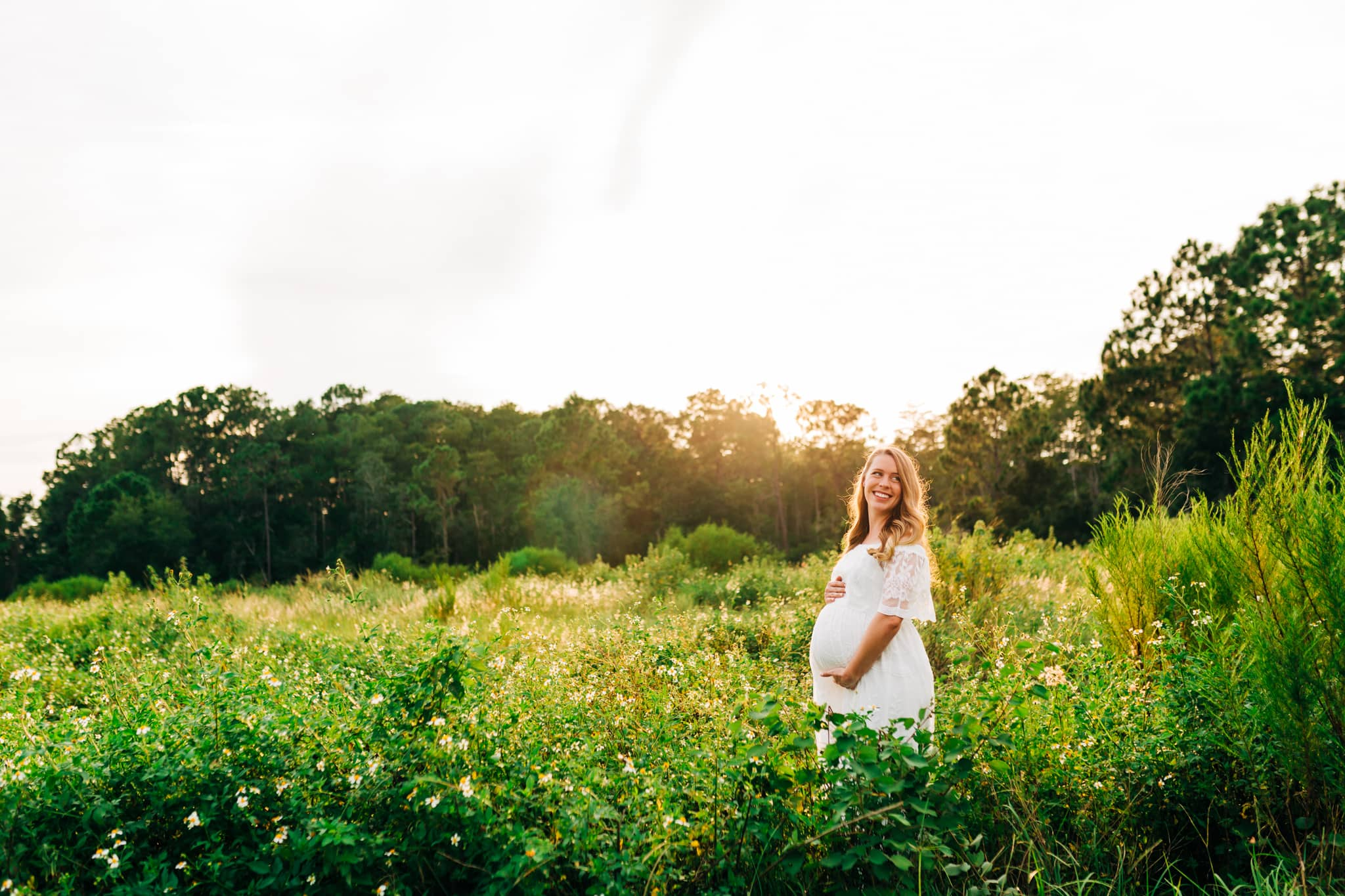 pregnant woman standing in field in white dress with the sun setting behind her in a florida state park