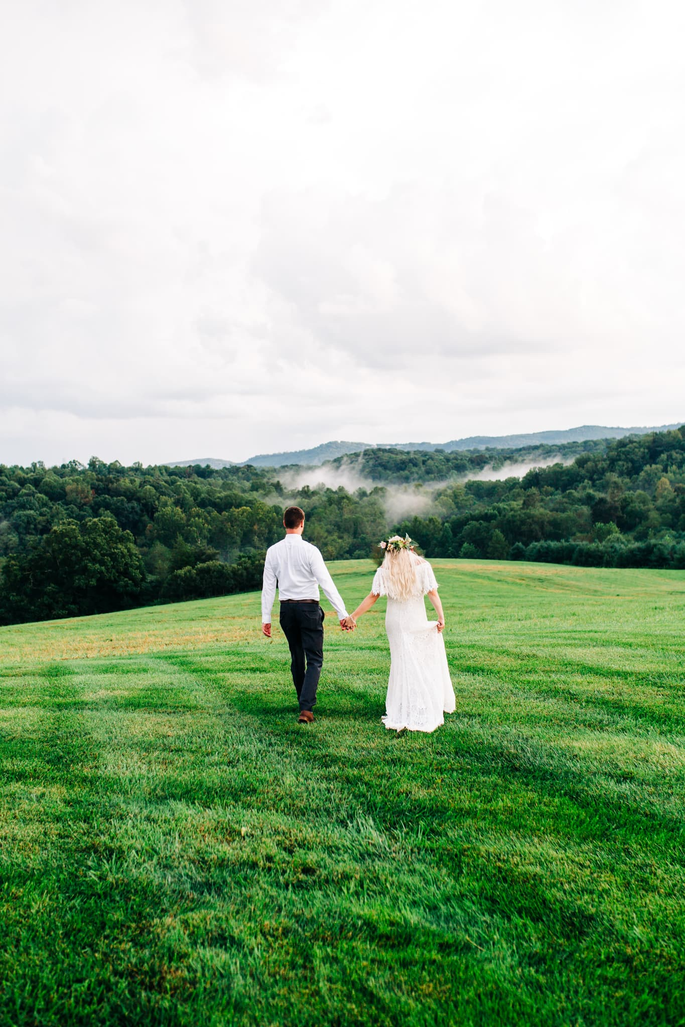 bride and groom holding hands with view of smoky mountains