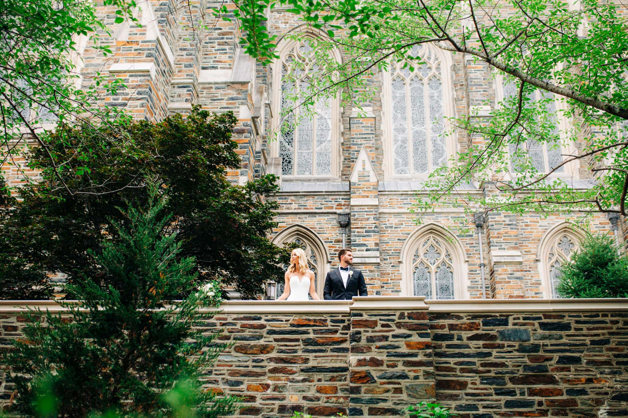 bride and groom holding hands in front of the duke chapel with trees and stones surrounding them