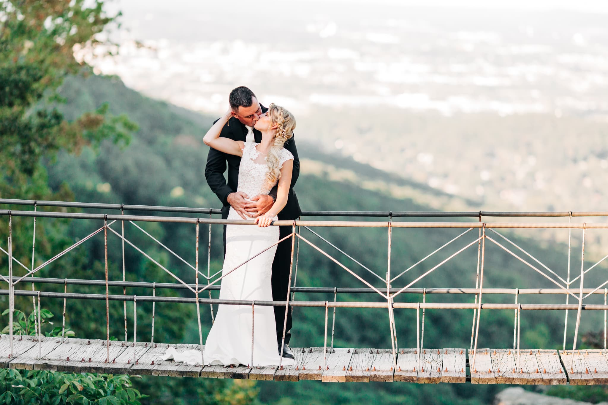 bride and groom kissing on a bride hanging over the mountains in Chattanooga Tennessee at the Grandview wedding venue