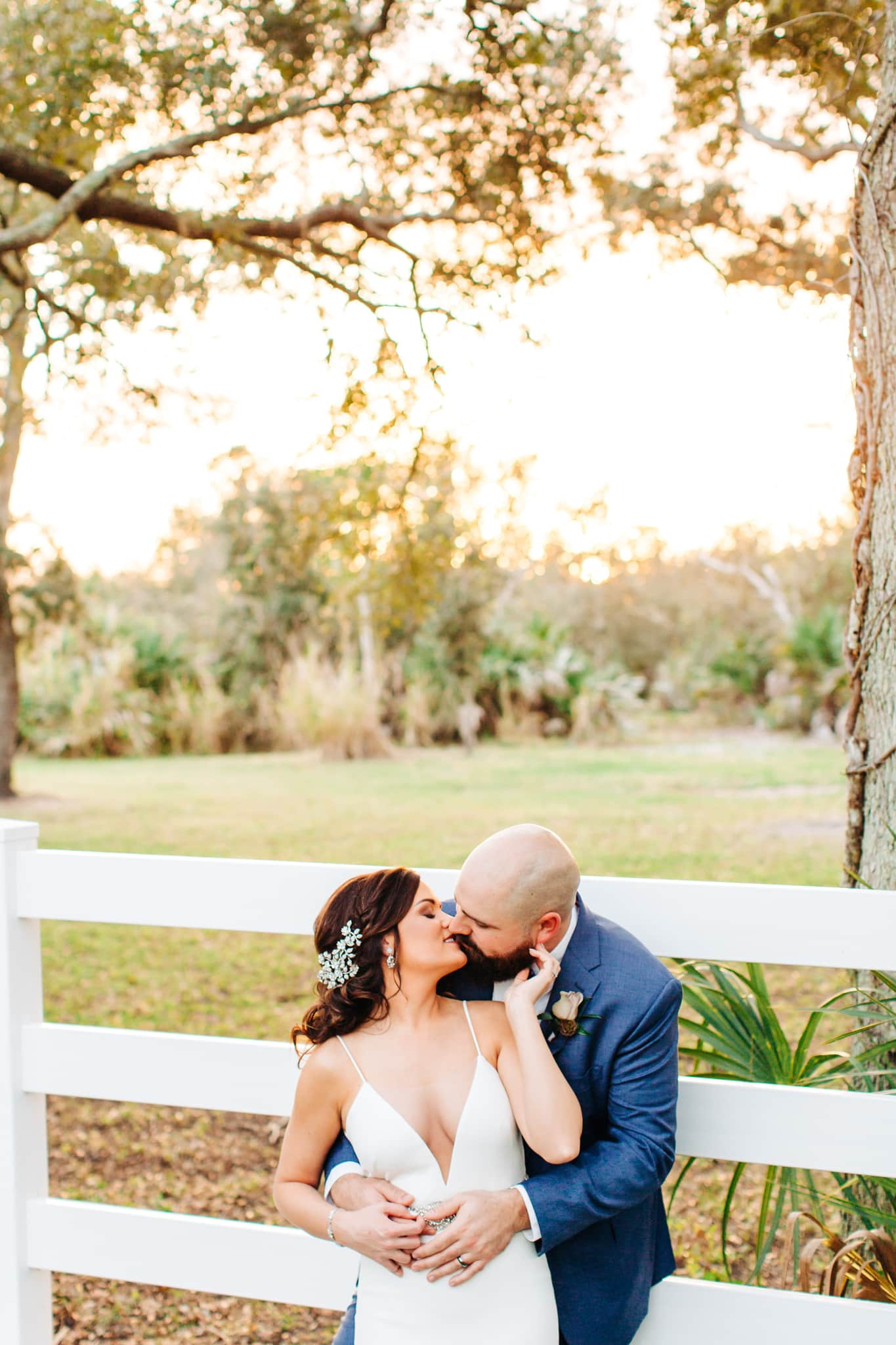 bride in low v cut gown kissing groom in navy blue suit along fence at up the creek farms with sun setting in background