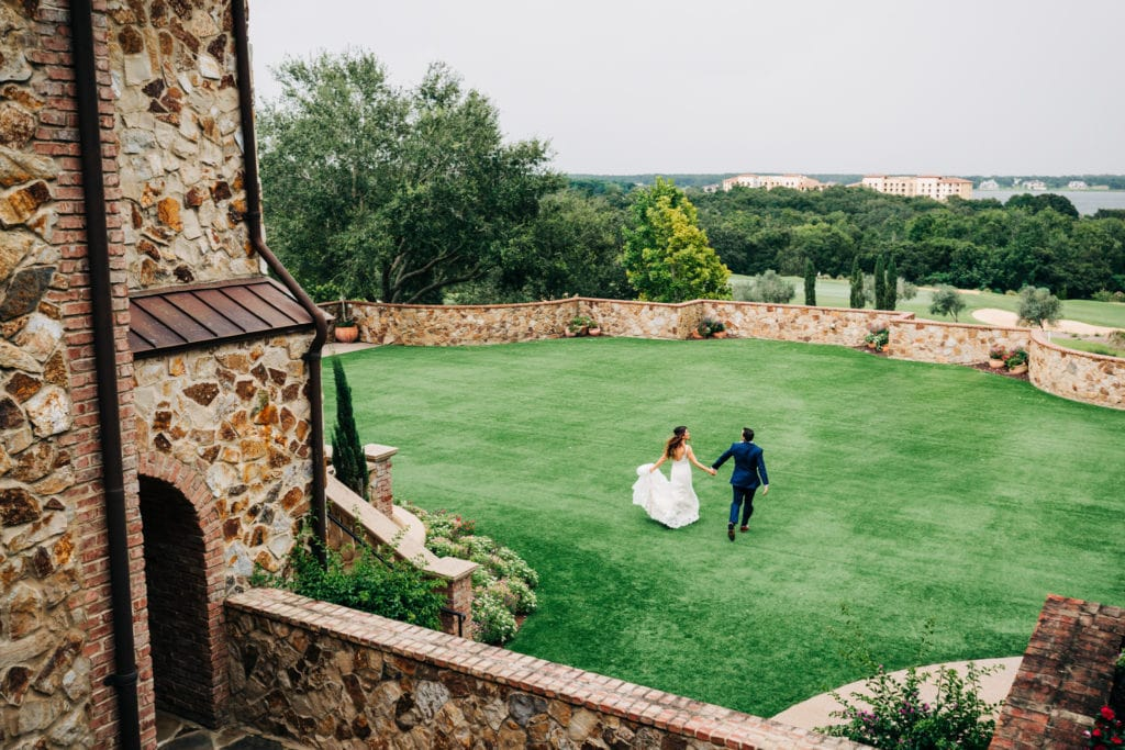 bride and groom running across lawn at Bella Collina in a distance from above with
