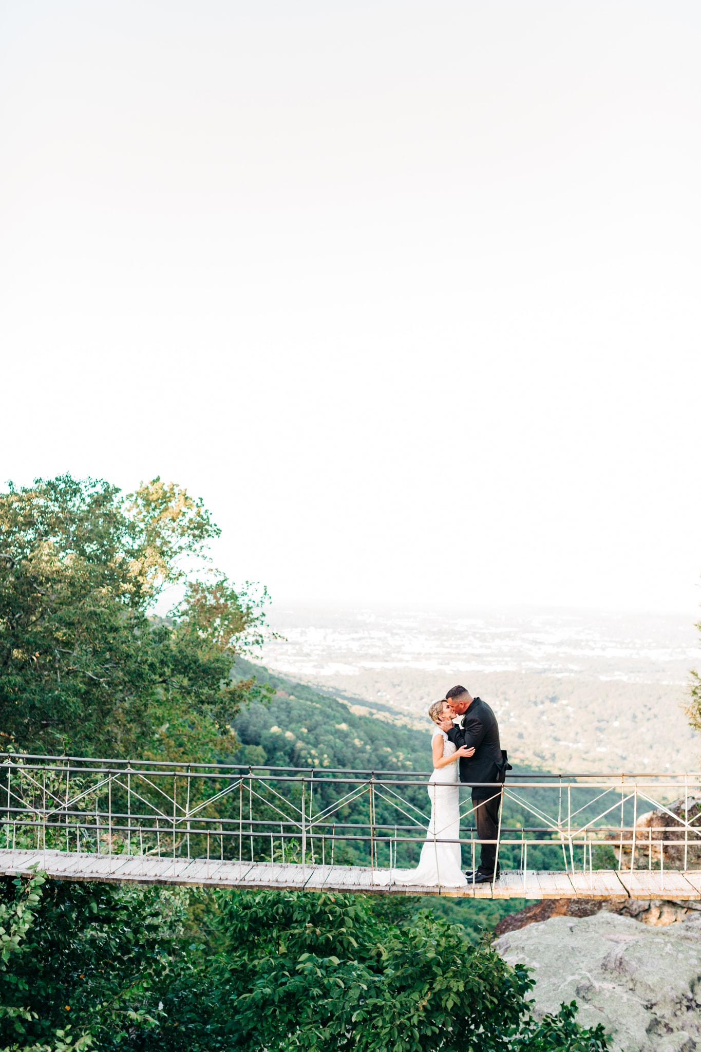 bride and groom kissing on bridge overlooking the mountains at the Grandview wedding venue
