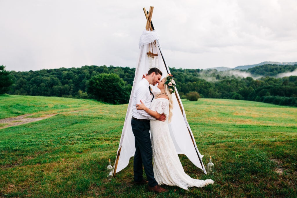 bride with flower crown kissing groom in front of teepee with smoky mountains in the background at gambill estate North Carolina