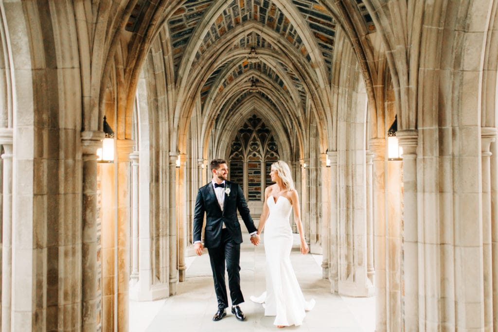 bride in vera wang dress and groom in custom suit walking under duke chapel hall together holding hands and smliing