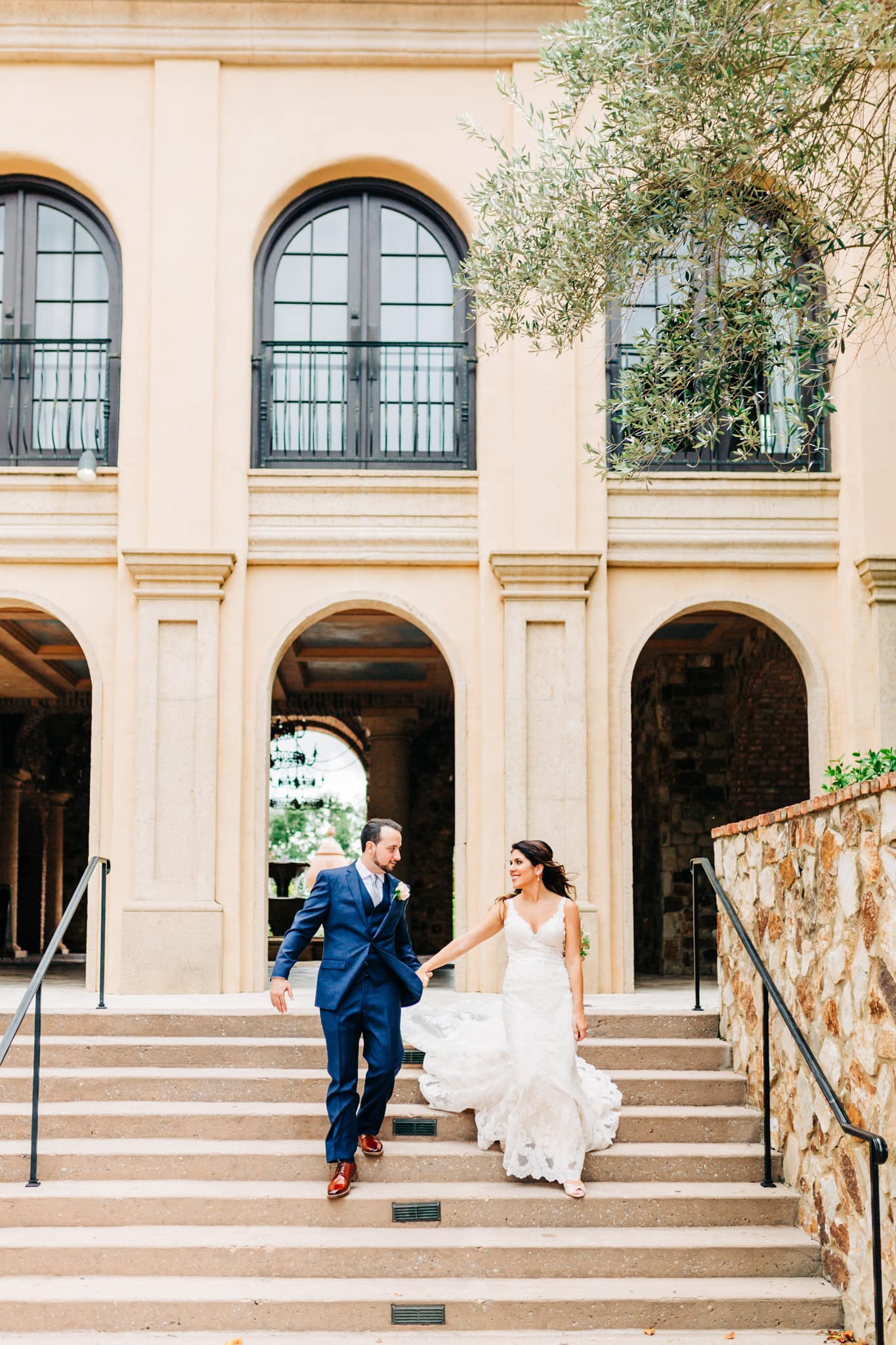 bride and groom running down the tuscan stairs at Bella Collina