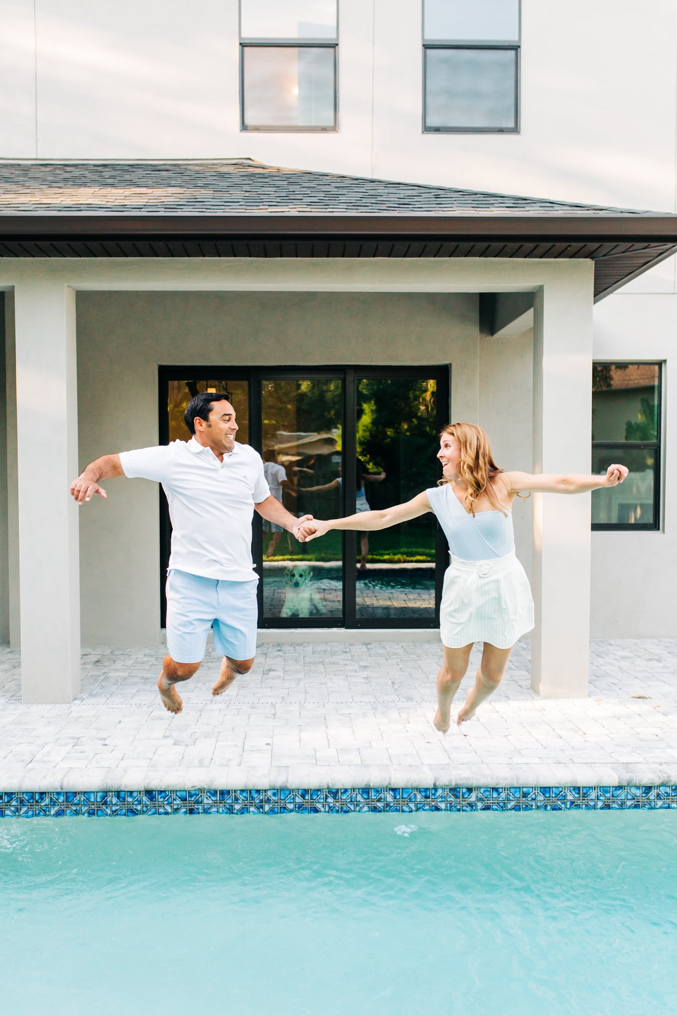 couple jumping into pool after buying a new house