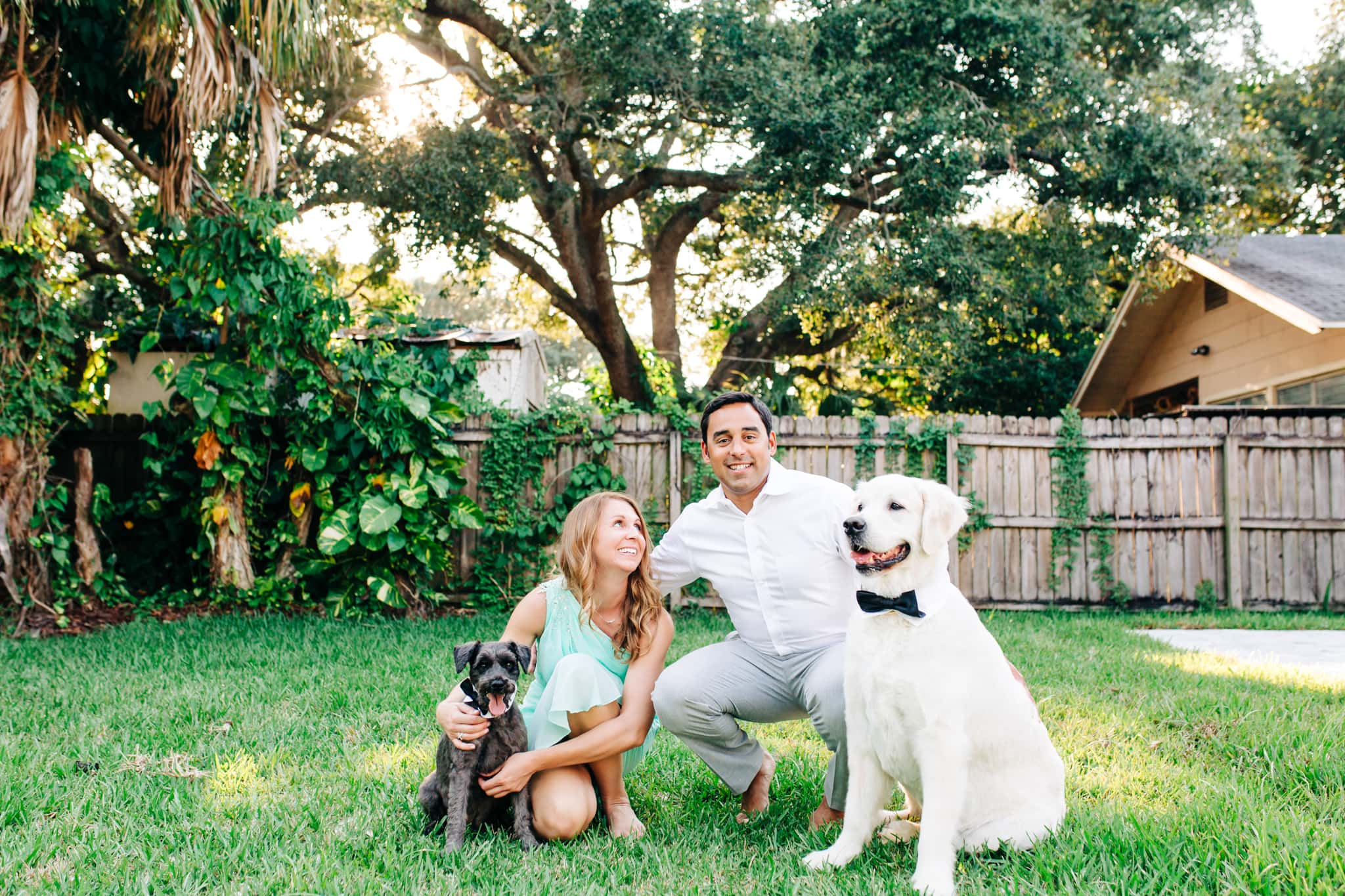 couple standing in backyard with their two dogs with the sun setting behind them