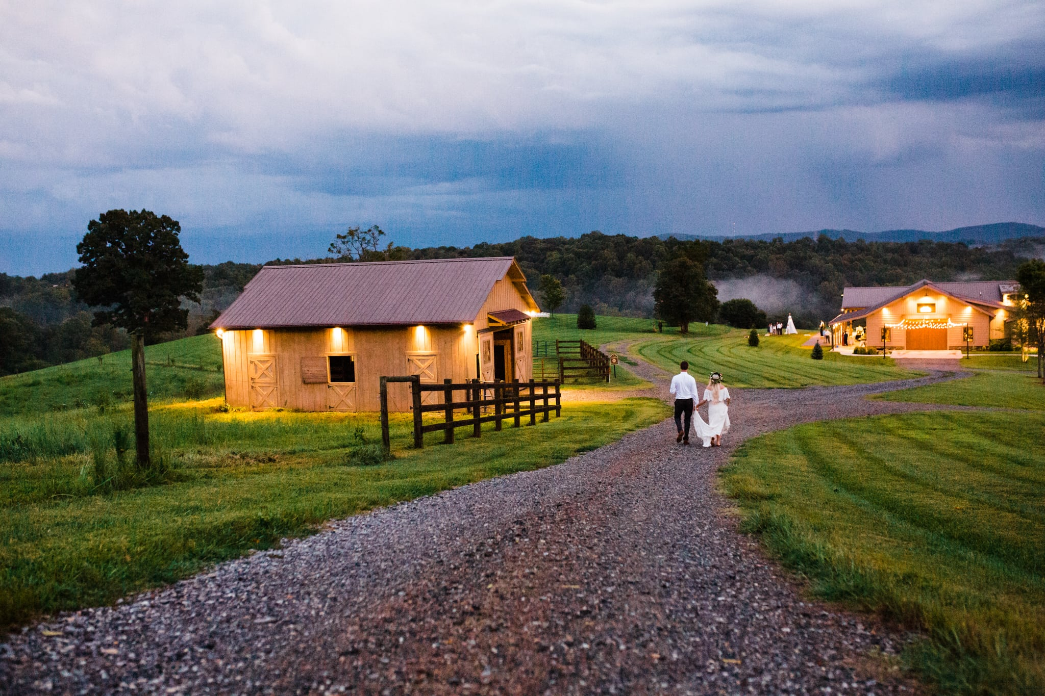 bride and groom walking down road during sunset lit by orange lights at gambill estate