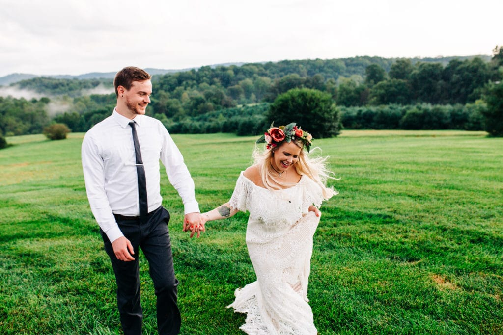 boho bride with flower crown laughing and walking with groom while holding hands along the lawn of gambill estate wedding venue in roaring river North Carolina