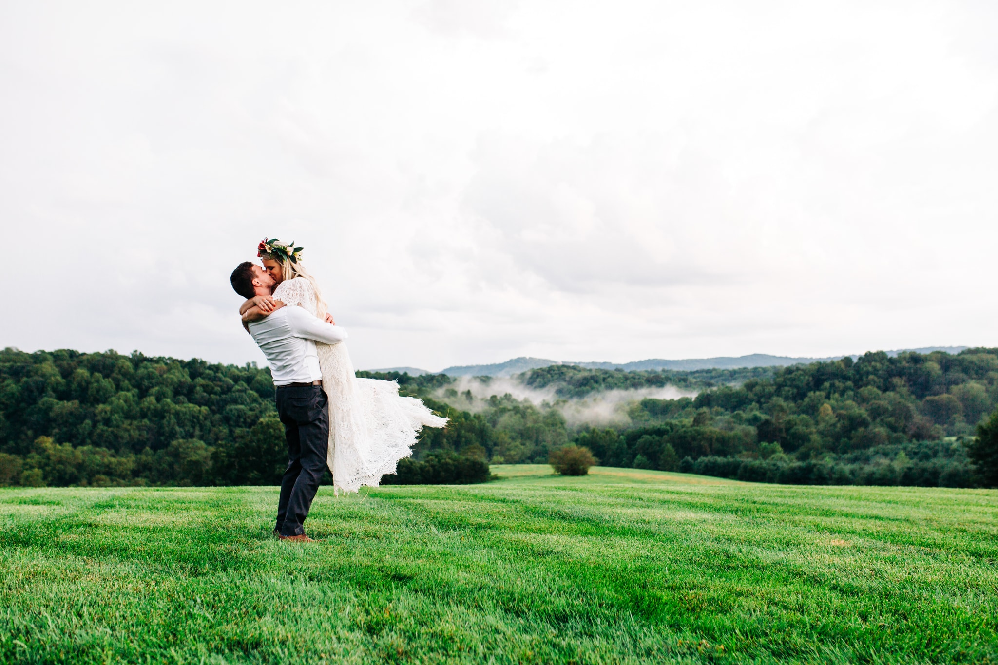 boho bride with flower crown being lifted in air by groom while kissing on the top of a hill at gambill estate with a view of the smoky mountains behind them