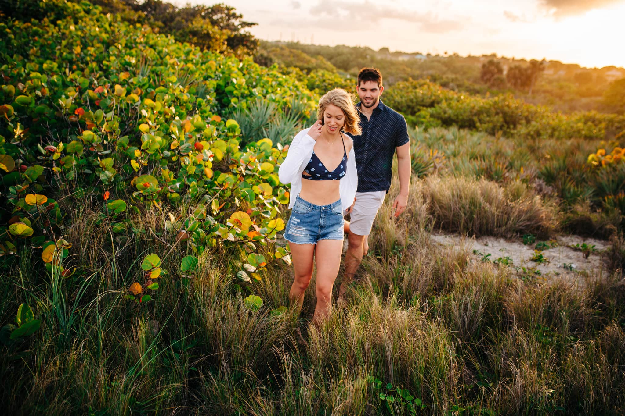 girl in bathing suit and shorts leading boyfriend through a field during golden hour
