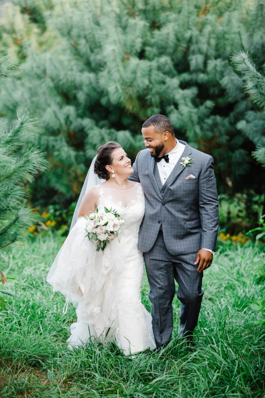 bride and groom walking through lush green trees and wildflowers on the side of gambill estate wedding venue