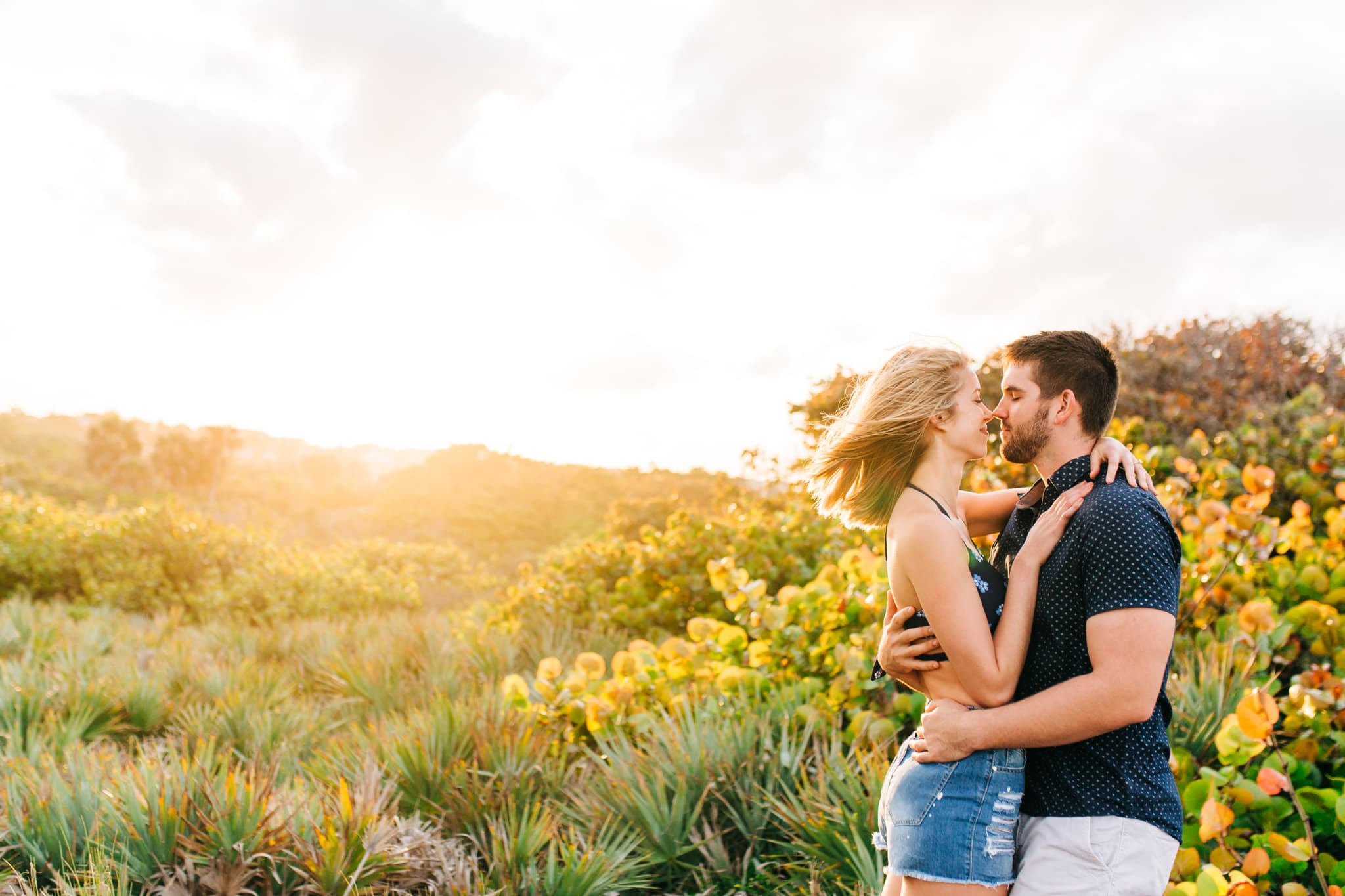 summertime engagement session with boy and girl kissing and sun beaming behind them