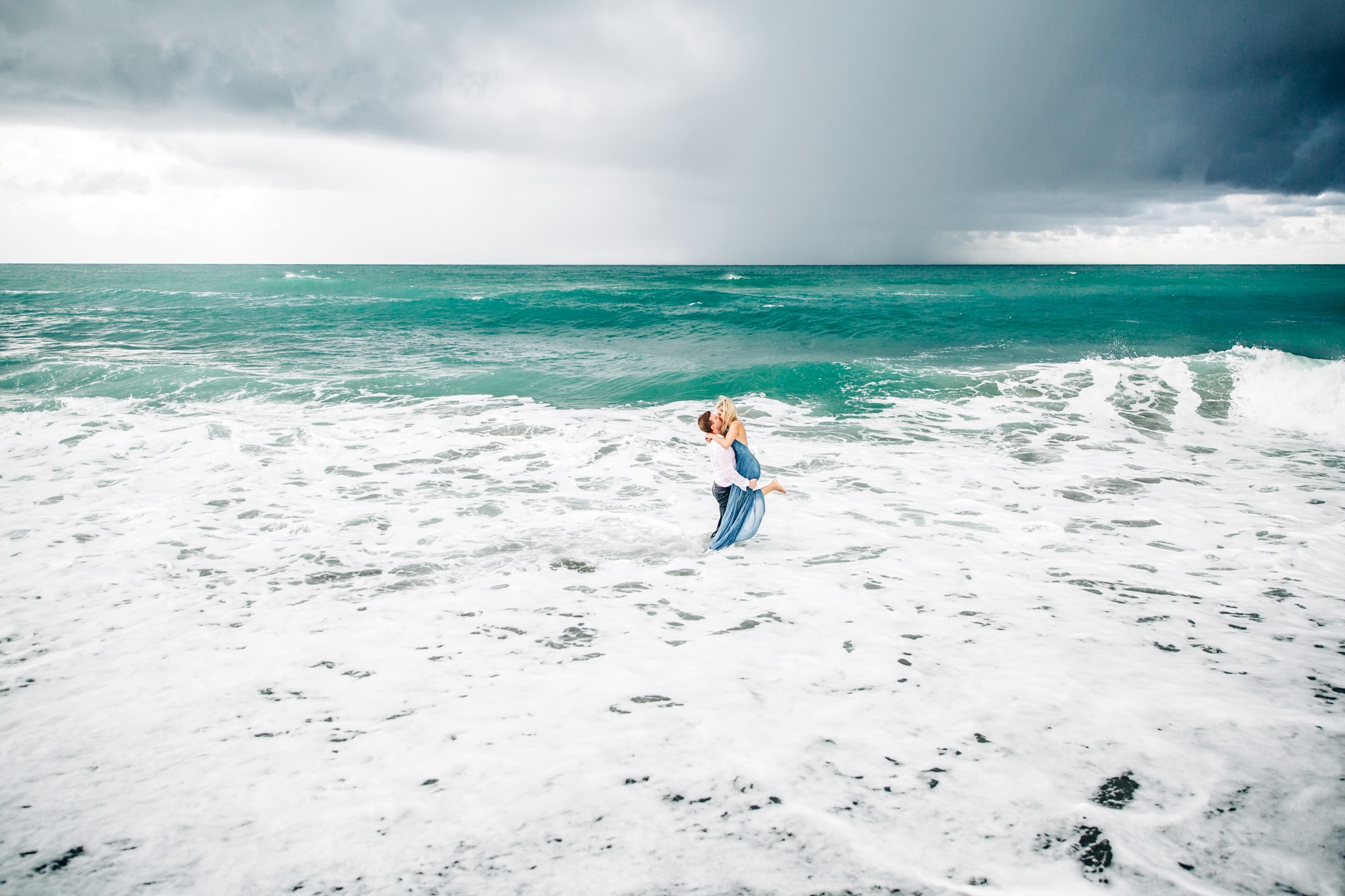 couple kissing in the middle of the ocean with a storm in the background at blowing rocks
