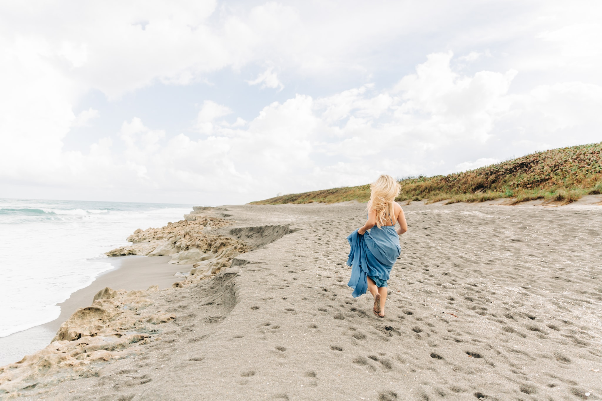 woman running down the beach in a blue dress with a storm on the horizon