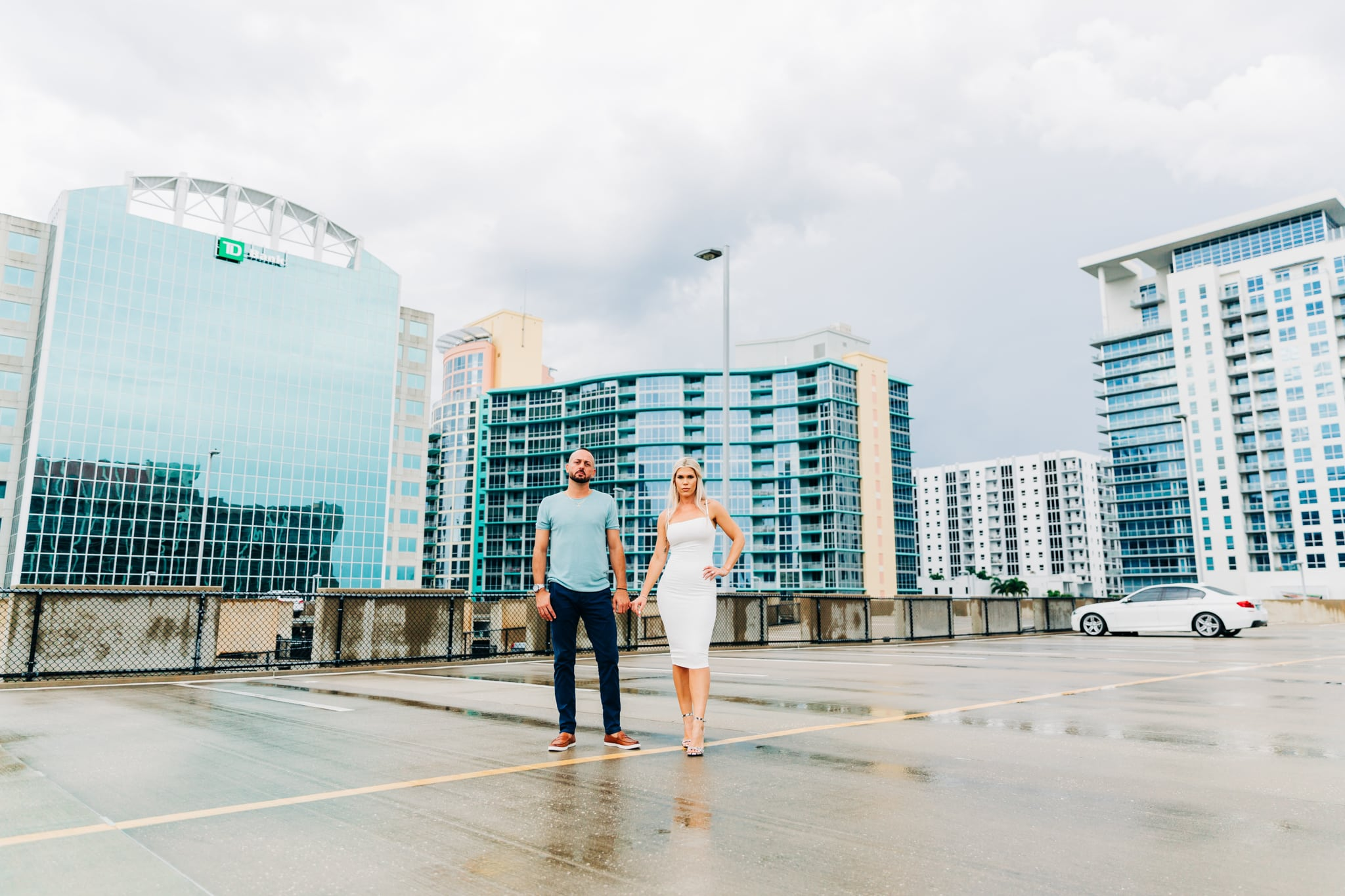 couple holding hands on rooftop in Downtown Orlando with white bmw in background