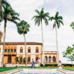 man leading woman along the infinity pool at ringling museum with palm trees and pink building in background