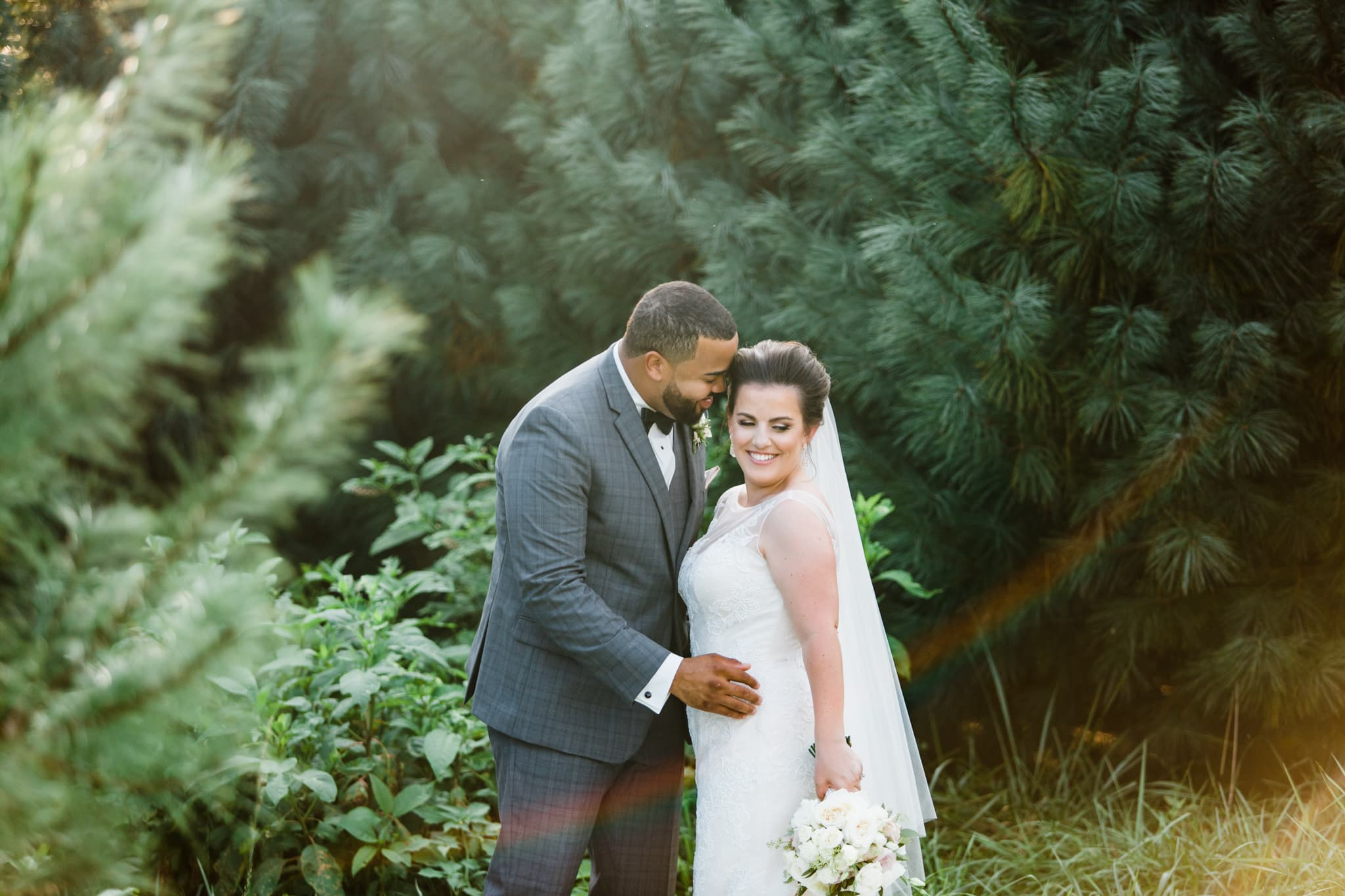 bride and groom tucked away into the woods and green trees of gambill estate during golden hour at sunset