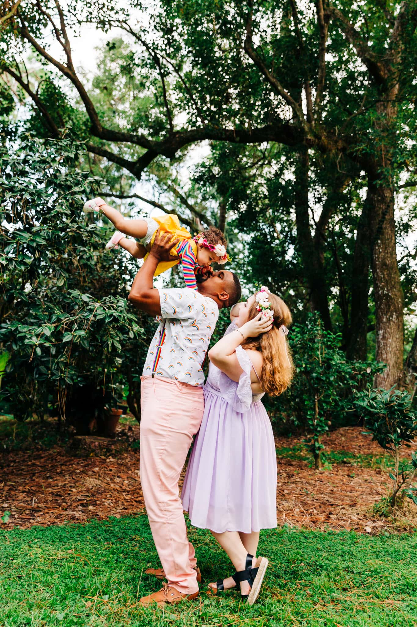boho family lifting baby up in the air with flower crowns and unicorns