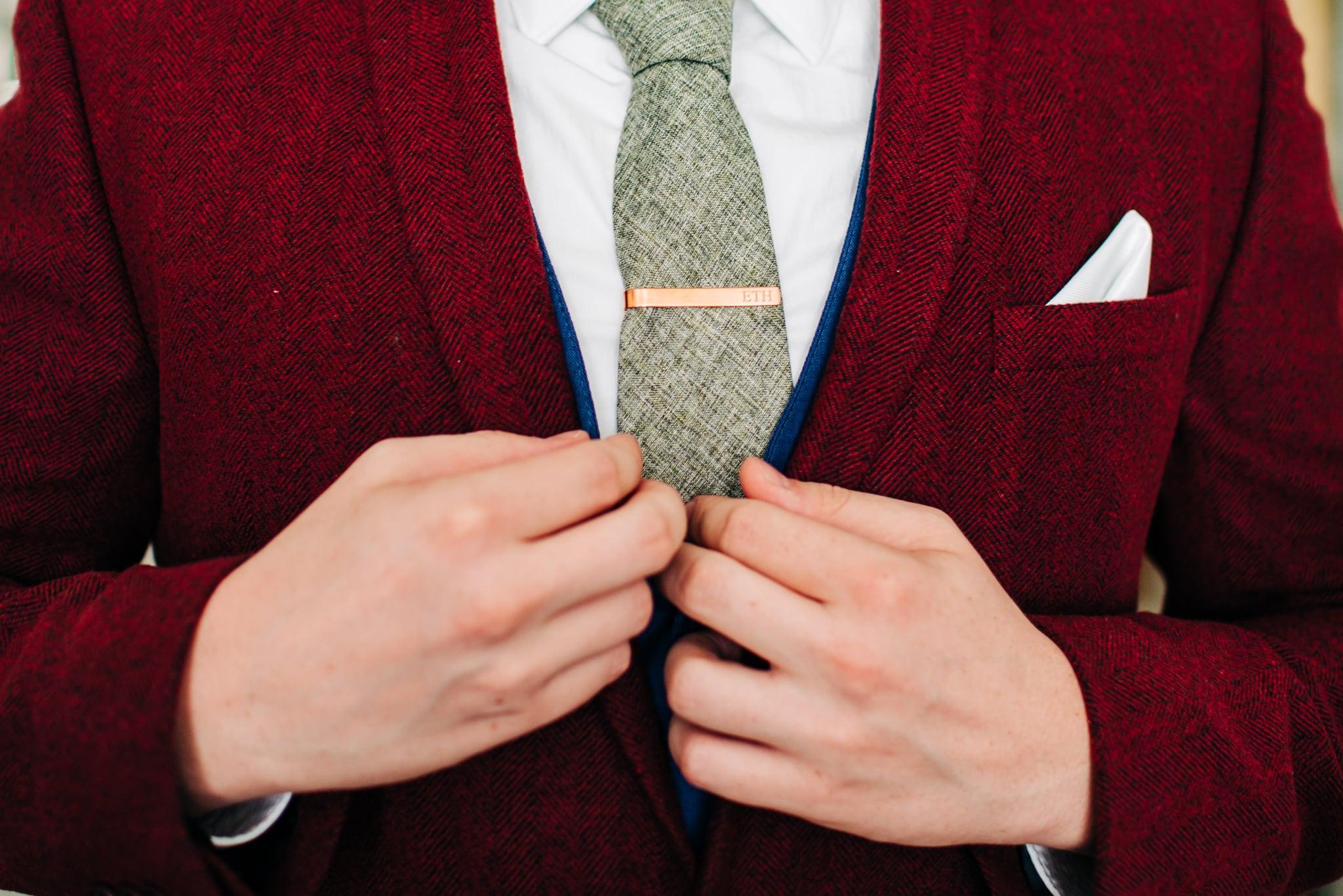 groom adjusting lapel on custom red velvet suit with gold tie clip