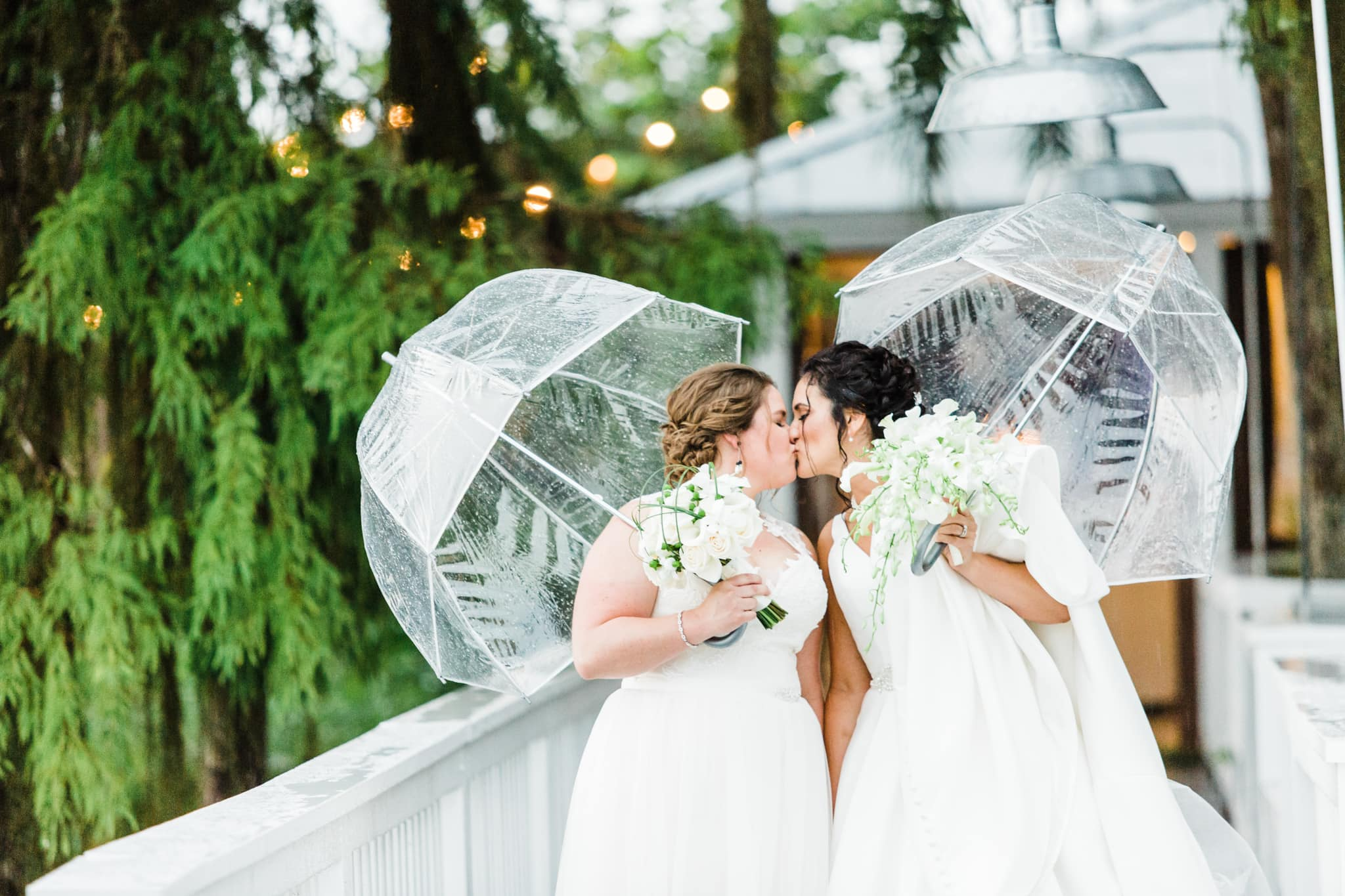 two brides kissing in the rain under clear bubble umbrellas