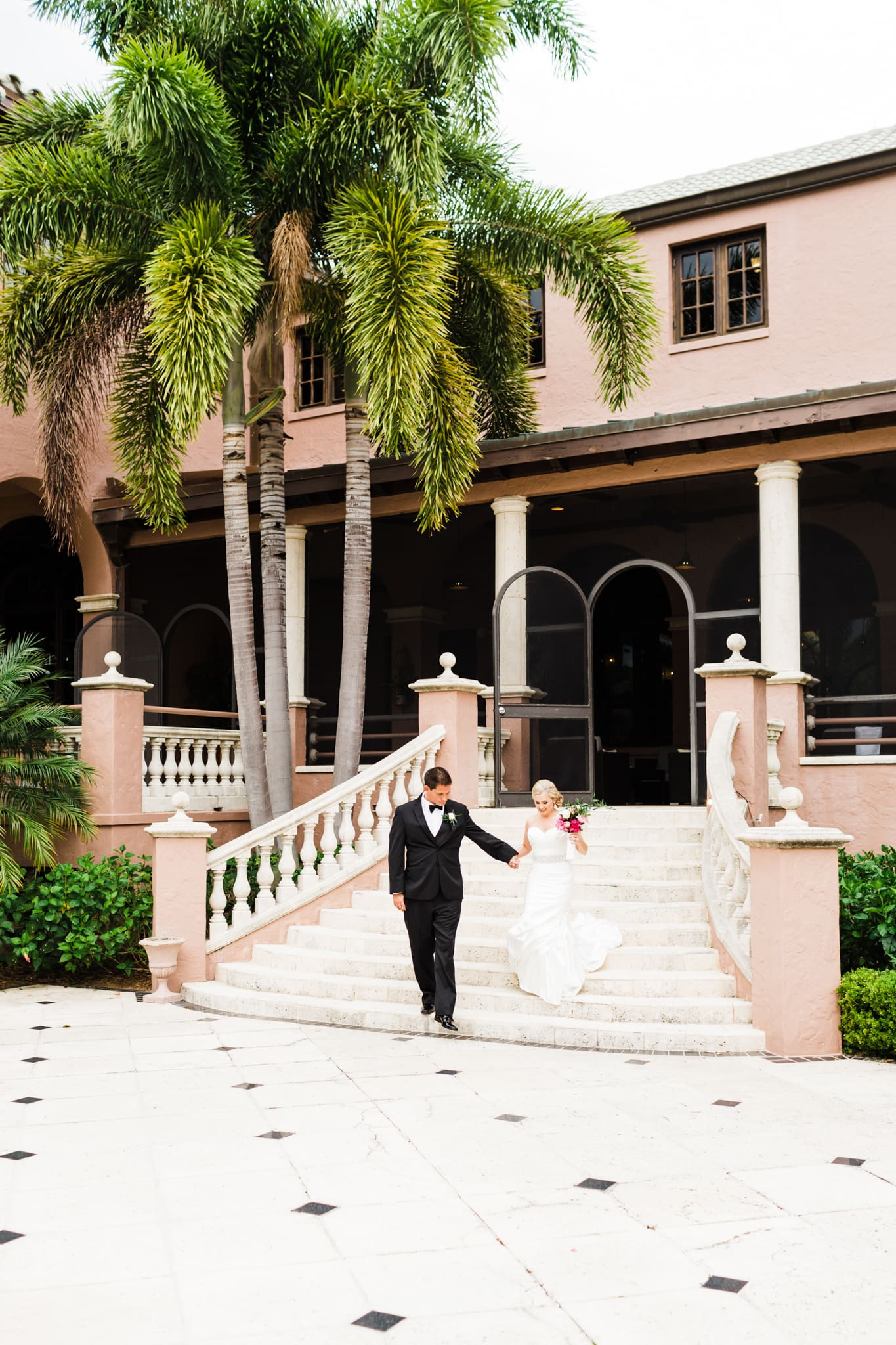 groom leading bride down the white stairs of the country club with a pink building and lush palm trees behind them