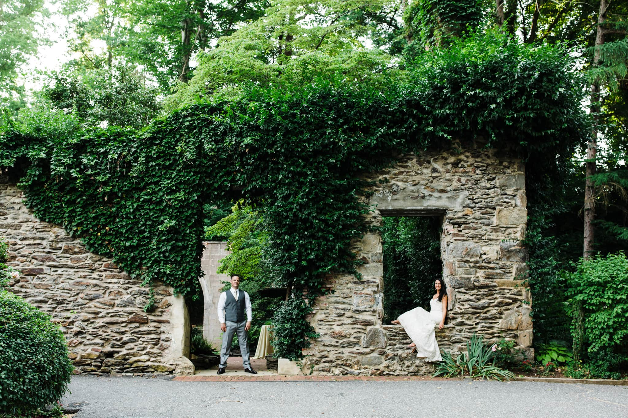 bride sitting in window of stone structure with groom standing in doorway and live green plants growing all around