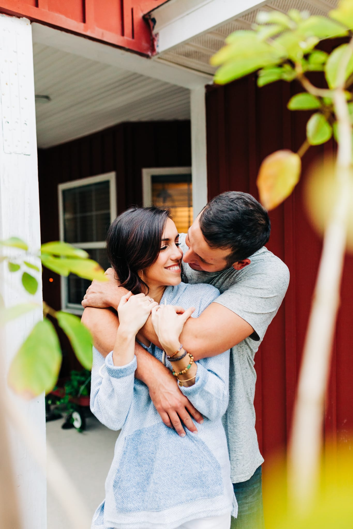 couple embracing in front of their red home between the trees