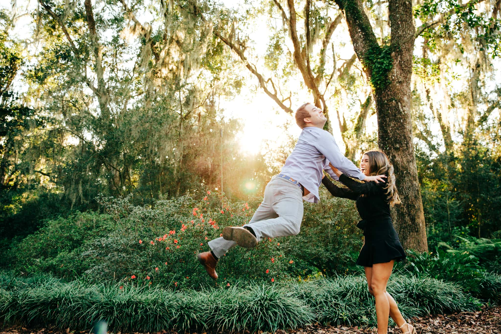 boyfriend leaping into the arms of his girlfriend with the sun shining behind them at box tower gardens