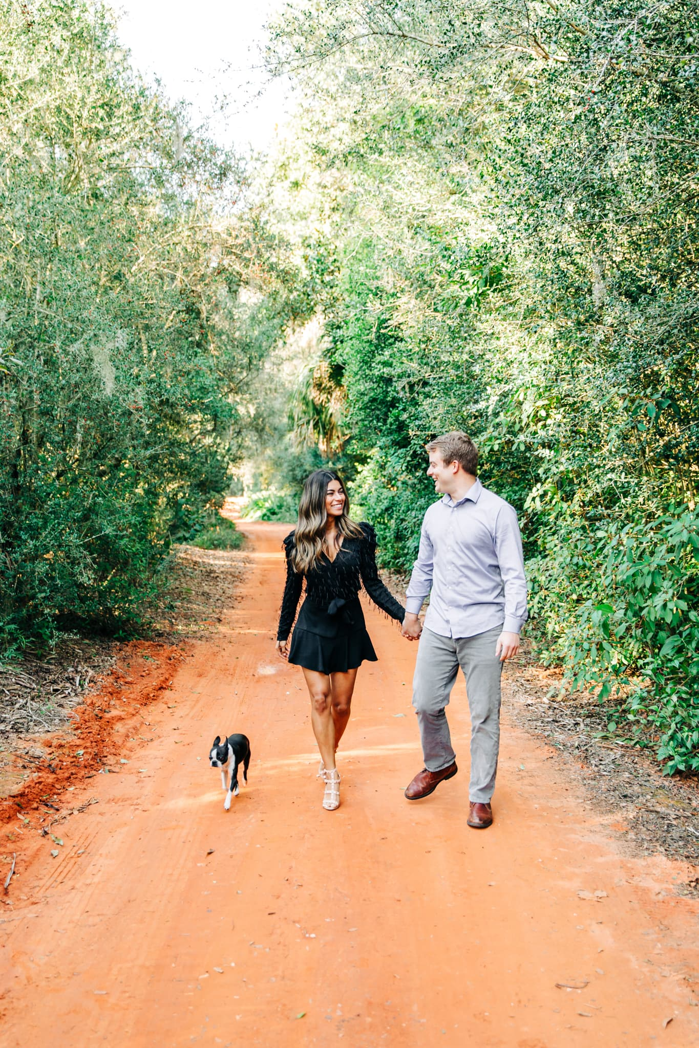 couple walking with small dog on red clay trail and lush green trees