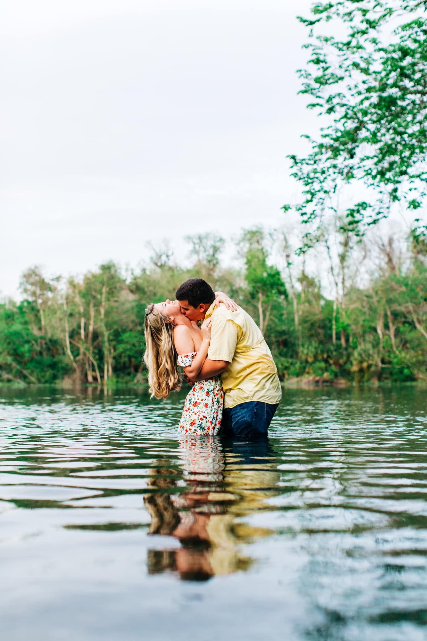 bride and groom kissing in the blue waters of wekiwa springs surrounded by trees