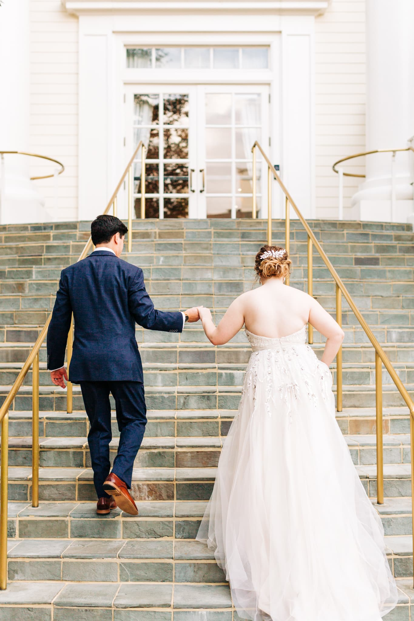 groom leading a bride up the stairs by hand at the Disney boardwalk