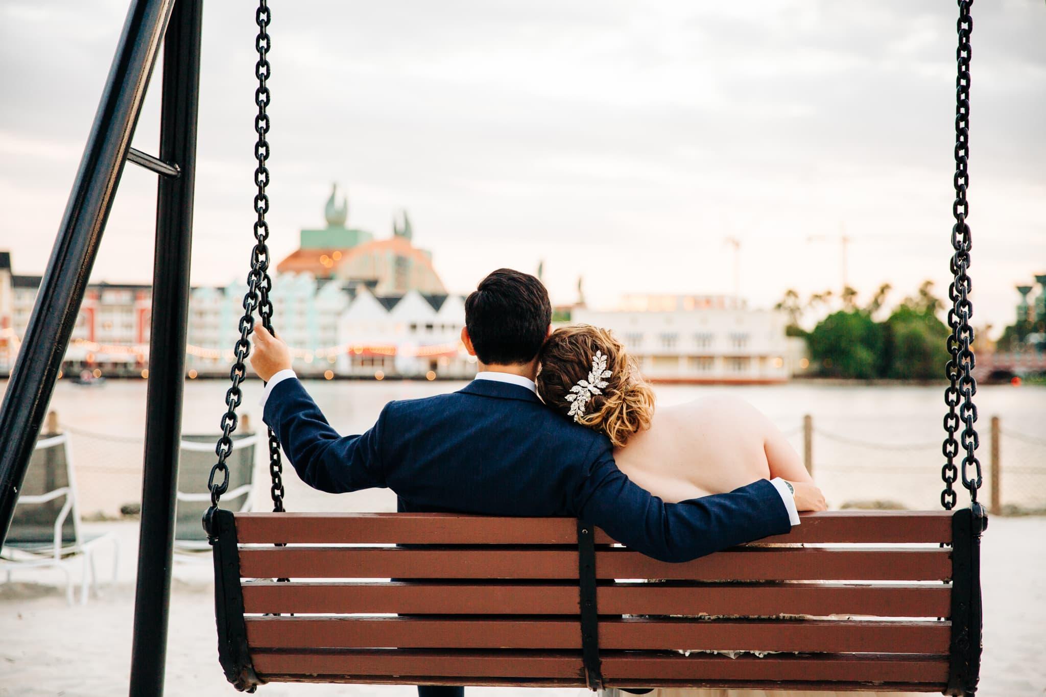 bride resting head on grooms shoulder while on swing overlooking Disney boardwalk